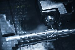 The abstract scene of CNC lathe machine milling the metal shaft and the G-code data background. The hi-technology automotive parts manufacturing process by royalty free stock photo