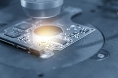 The abstract scene of the electronics circuit board . The electronics circuit board with the telescopic camera for quality control.Computer part manufacturing royalty free stock photo