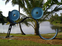Abstract sculptures by lake. Closeup of abstract modern sculptures in tropical park with lake in background Royalty Free Stock Images