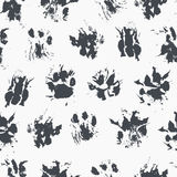 Abstract seamless pattern - black ink prints with messy cat paws. Royalty Free Stock Photos