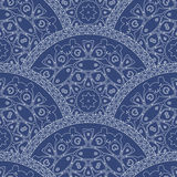 Abstract seamless wavy pattern from decorative ethnic ornaments with dark blue paint texture. Regular fan or peacock tail shaped o. Rnamental elements Stock Image