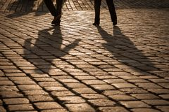 Shadows of people walking on an old street. Abstract shadows of people walking on an old street Royalty Free Stock Image