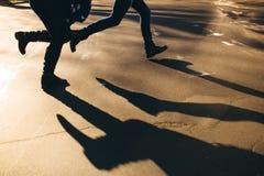 Abstract shadows of running couple on street Stock Photo