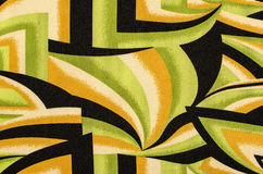 Abstract shapes pattern on fabric. Green with black and yellow geometric spyral shapes material as background Stock Image