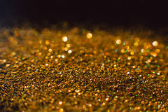 Abstract shining glitters golden holiday backdrop. Abstract shining glitters golden holiday bokeh background with copy space. Defocused lights backdrop Stock Image