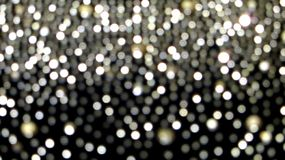 Abstract  shiny lights on the black background. Abstract shiny lights bokeh on the black background which are fallling like magic snow from the sky in the stock photography