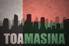 Abstract silhouet van de stad met tekst Toamasina bij de uitstekende vlag van Madagascar Stock Afbeelding