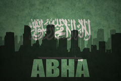 Abstract silhouette of the city with text Abha at the vintage saudi arabia flag Royalty Free Stock Photos