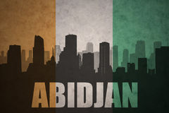 Abstract silhouette of the city with text Abidjan at the vintage ivorian flag. Background Royalty Free Stock Photo