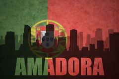 Abstract silhouette of the city with text Amadora at the vintage portuguese flag. Background Stock Photos