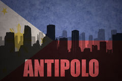 Abstract silhouette of the city with text Antipolo at the vintage philippines flag. Background royalty free stock image