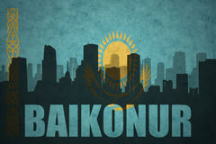 Abstract silhouette of the city with text Baikonur at the vintage kazakhstan flag. Background royalty free stock photography