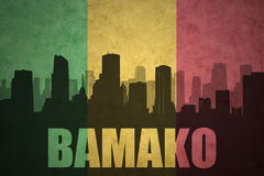 Abstract silhouette of the city with text Bamako at the vintage malian flag. Background royalty free stock photo