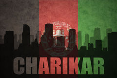 Abstract silhouette of the city with text Charikar at the vintage afghanistan flag Stock Images
