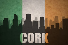 Abstract silhouette of the city with text Cork at the vintage irish flag Stock Photos