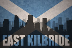 Abstract silhouette of the city with text East Kilbride at the vintage scotland flag. Background stock photo