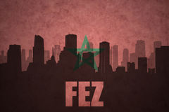 Abstract silhouette of the city with text Fez at the vintage moroccan flag. Background Stock Photography