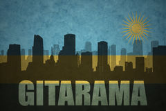 Abstract silhouette of the city with text Gitarama at the vintage rwandan flag. Background Stock Images