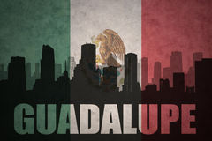 Abstract silhouette of the city with text Guadalupe at the vintage mexican flag. Background Royalty Free Stock Image