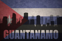 Abstract silhouette of the city with text Guantanamo at the vintage cuban flag. Background Stock Photos
