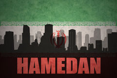 Abstract silhouette of the city with text Hamedan at the vintage iranian flag. Background Stock Photo