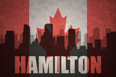 Abstract silhouette of the city with text Hamilton at the vintage canadian flag vector illustration