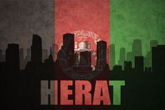Abstract silhouette of the city with text Herat at the vintage afghanistan flag Royalty Free Stock Photos