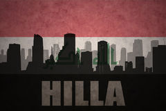 Abstract silhouette of the city with text Hilla at the vintage iraqi flag. Background Stock Photos