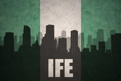 Abstract silhouette of the city with text Ife at the vintage nigerian flag Royalty Free Stock Photo