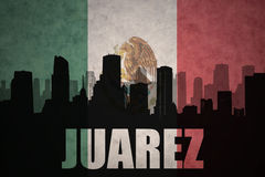Abstract silhouette of the city with text Juarez at the vintage mexican flag Royalty Free Stock Image