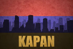 Abstract silhouette of the city with text Kapan at the vintage armenian flag Stock Photography
