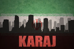 Abstract silhouette of the city with text Karaj at the vintage iranian flag. Background Royalty Free Stock Photography