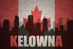 Abstract silhouette of the city with text Kelowna at the vintage canadian flag Royalty Free Stock Photo