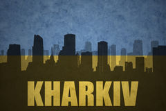 Abstract silhouette of the city with text Kharkiv at the vintage ukrainian flag Stock Images