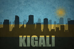 Abstract silhouette of the city with text Kigali at the vintage rwandan flag. Background Stock Photos