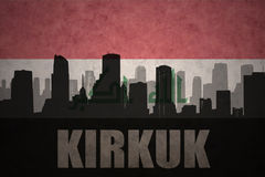 Abstract silhouette of the city with text Kirkuk at the vintage iraqi flag. Background Royalty Free Stock Images