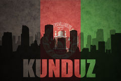Abstract silhouette of the city with text Kunduz at the vintage afghanistan flag. Background Stock Photos