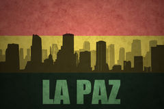 Abstract silhouette of the city with text La Paz at the vintage bolivian flag Royalty Free Stock Photo