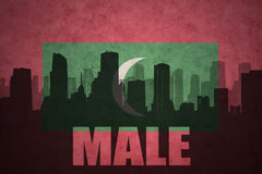 Abstract silhouette of the city with text Male at the vintage maldives flag Royalty Free Stock Images