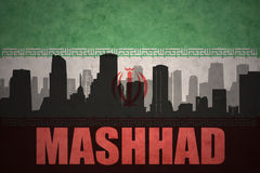 Abstract silhouette of the city with text Mashhad at the vintage iranian flag. Background Royalty Free Stock Image