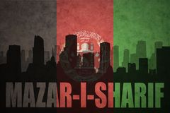 Abstract silhouette of the city with text Mazar-i-Sharif at the vintage afghanistan flag. Background Royalty Free Stock Image
