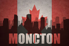 Abstract silhouette of the city with text Moncton at the vintage canadian flag Royalty Free Stock Photo