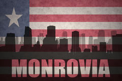 Abstract silhouette of the city with text Monrovia at the vintage liberian flag. Background Stock Images