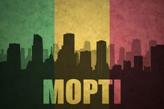 Abstract silhouette of the city with text Mopti at the vintage malian flag. Background stock photos