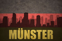 Abstract silhouette of the city with text Munster at the vintage german flag. Background Stock Image