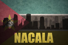 Abstract silhouette of the city with text Nacala at the vintage mozambican flag. Background Royalty Free Stock Photo