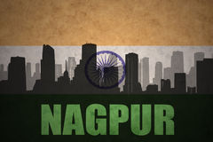 Abstract silhouette of the city with text Nagpur at the vintage indian flag. Background Stock Photography