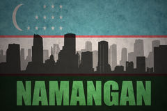 Abstract silhouette of the city with text Namangan at the vintage uzbekistan flag. Background royalty free stock photo