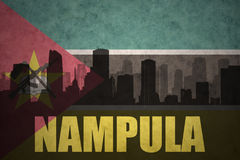 Abstract silhouette of the city with text Nampula at the vintage mozambican flag. Background Royalty Free Stock Image