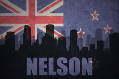 Abstract silhouette of the city with text Nelson at the vintage new zealand flag. Background Stock Images